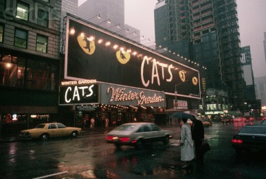 """September 1989 --- Lights shine on a billboard advertising the Broadway show """"Cats"""" over the Winter Garden theater in New York City. 